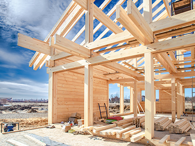 Wooden House frame, with blue sky in the background.